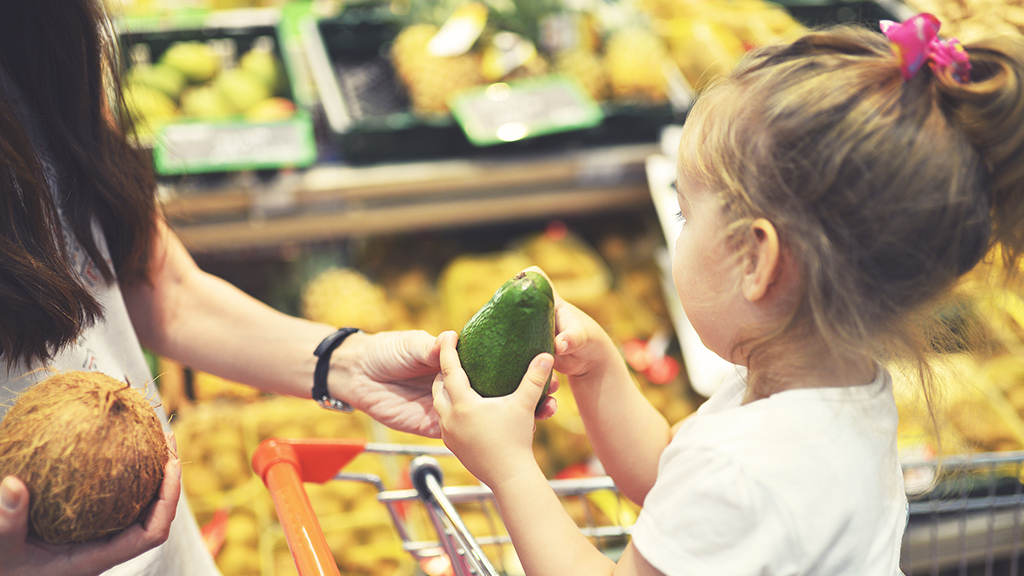 Child examining produce at a grocery store - Sanford fit