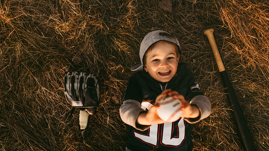 Young boy lying in grass holding baseball-Sanford Fit