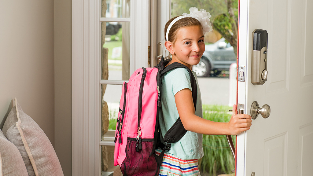 Girl walking out of the door with her backpack on - Sanford fit