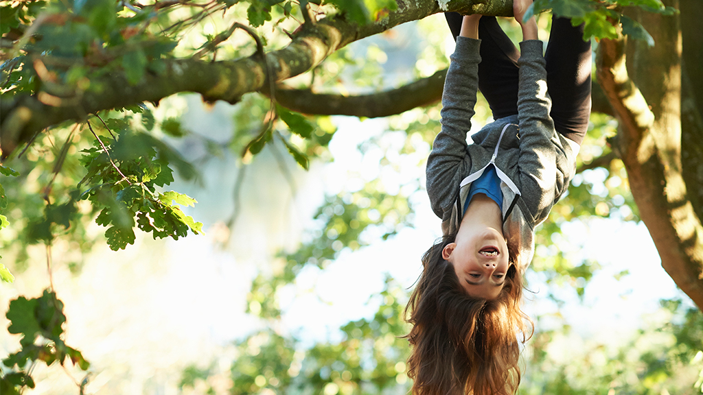 Girl hangs from tree upside down