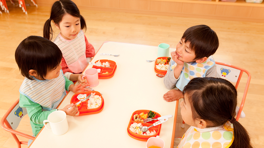 Four children sitting at a kid-sized table enjoying a meal - Sanford fit