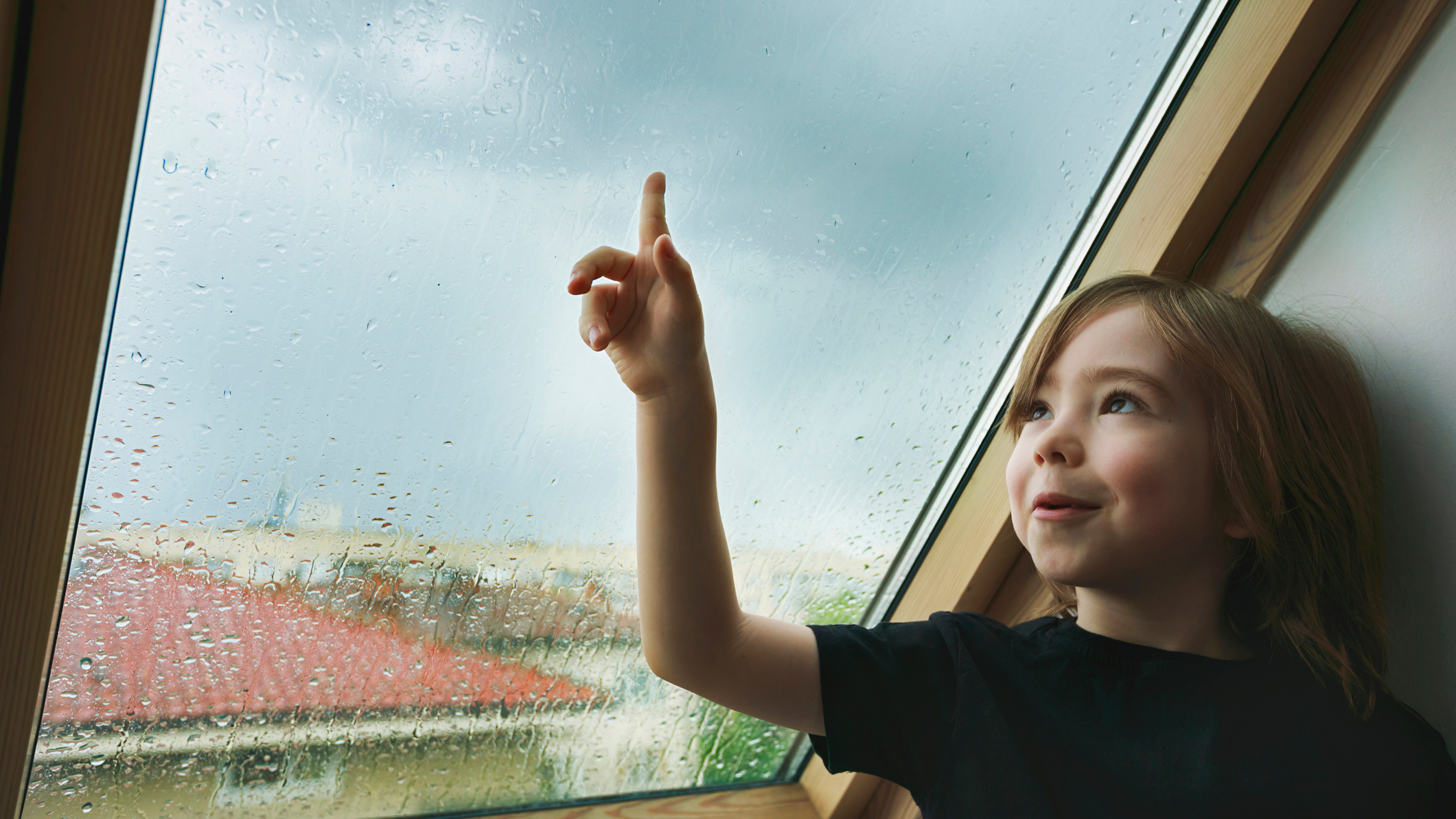Child looks out the window at the rain