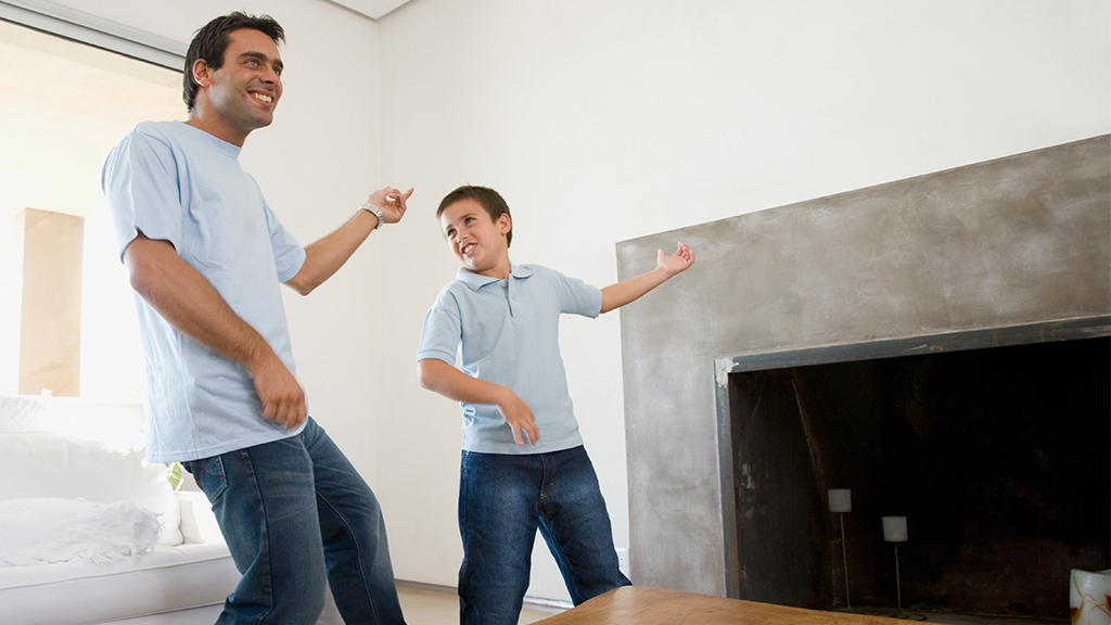 Father and son play air guitar in the living room