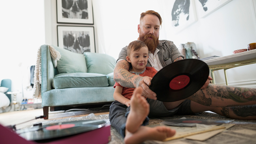 guardian and son sitting on floor within home looking at music records-Sanford fit