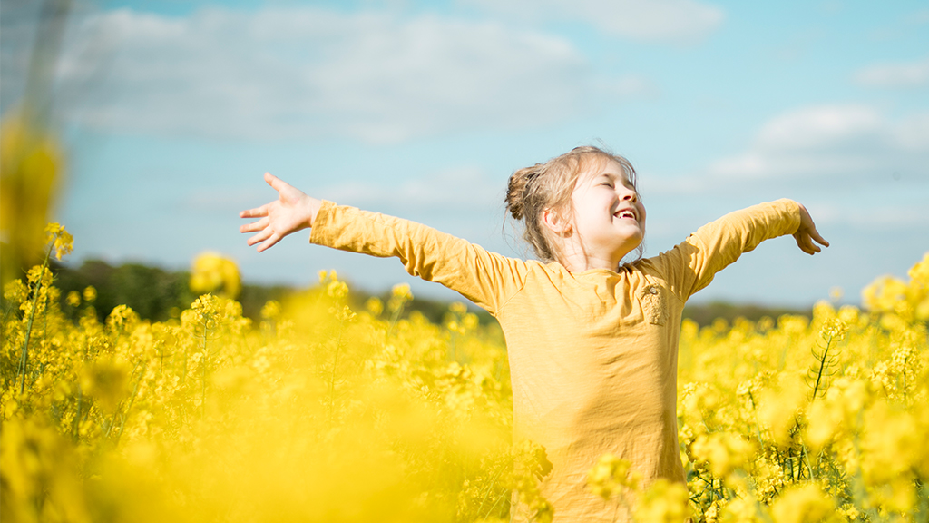 Girl stands in flower field