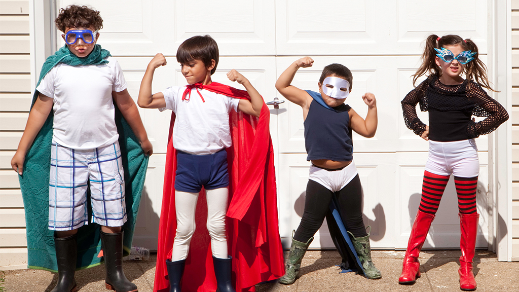 Group of four kids pose while wearing super hero costumes