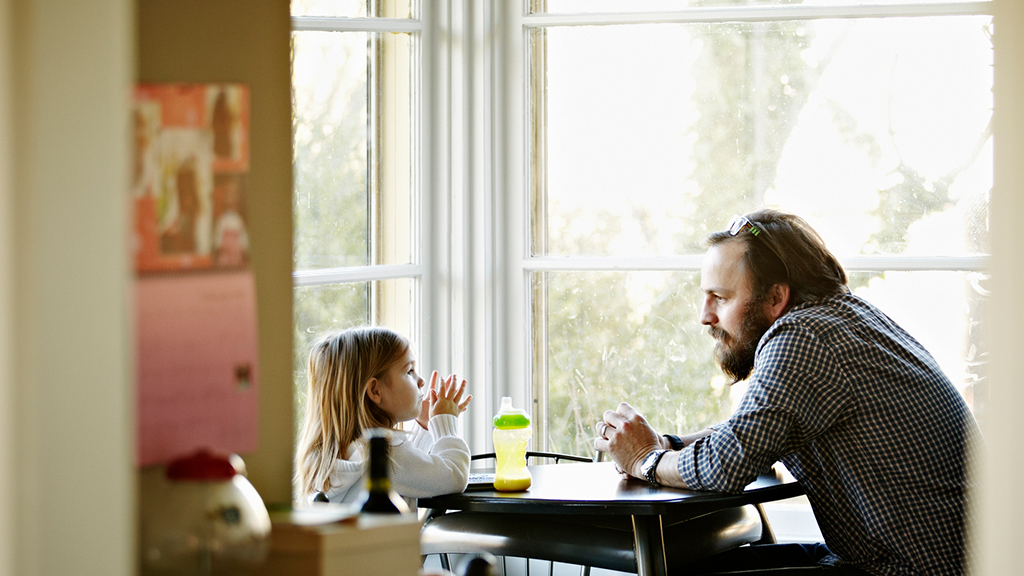 Father and daughter sit at dinner table to talk