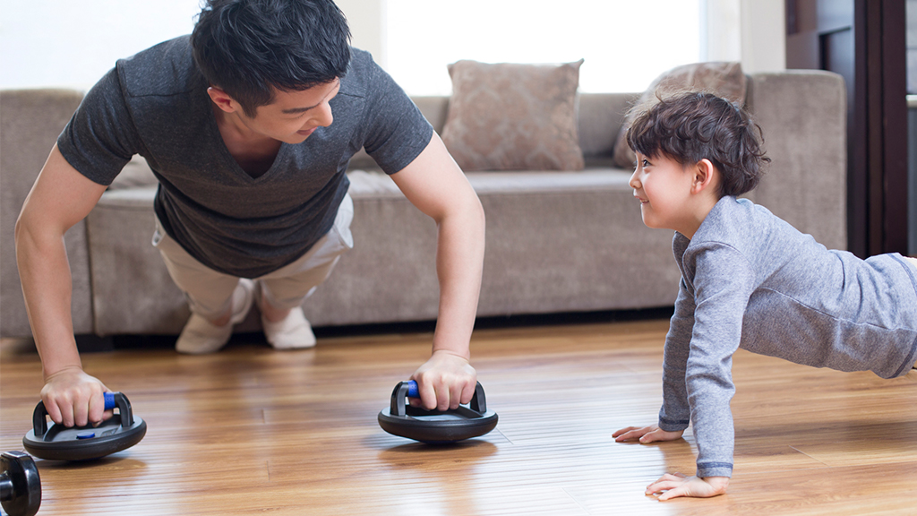 Boy and his father practice push ups at home