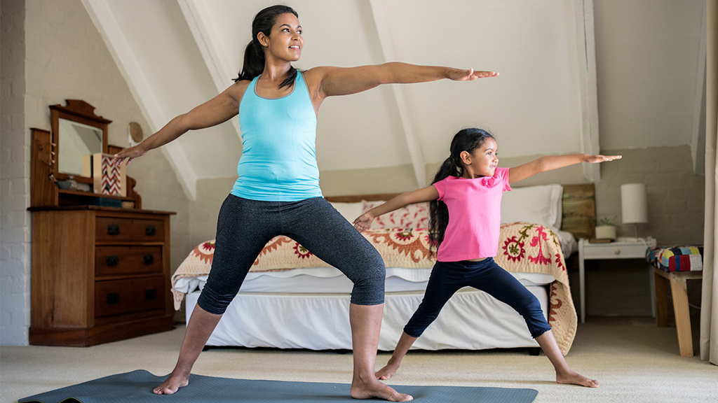 A mother and her daughter go into the Warrior Pose