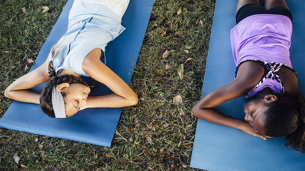 Girls relaxing on yoga mats outside