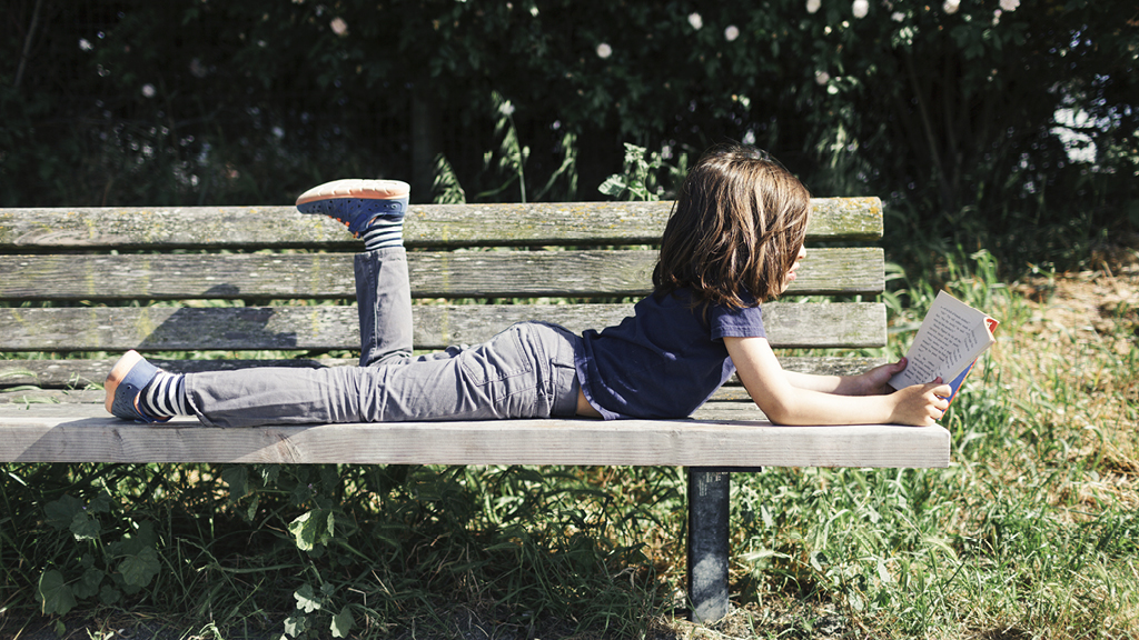 Child relaxing while reading outside on a bench.