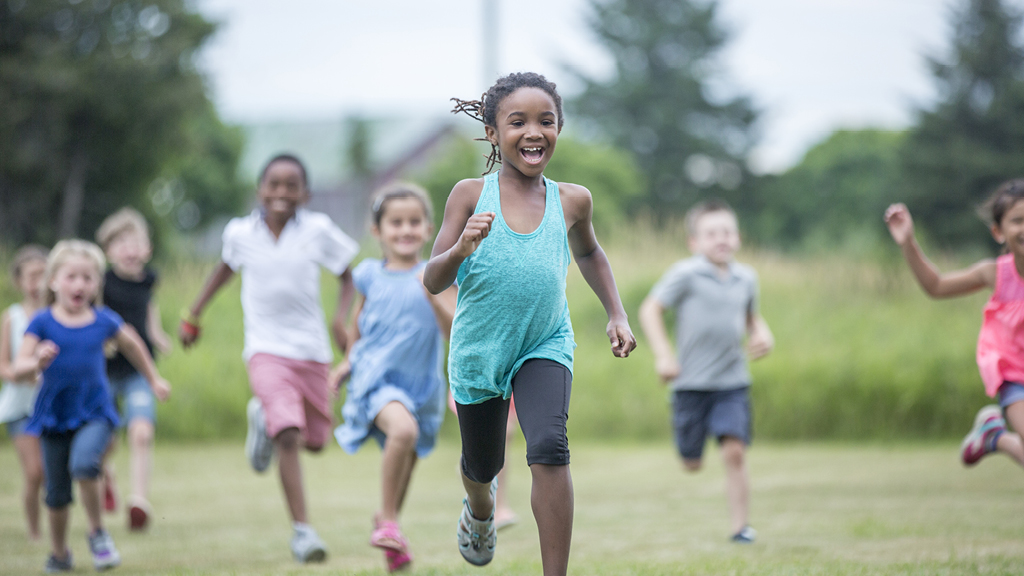 Group of kids running outside on a grassy field