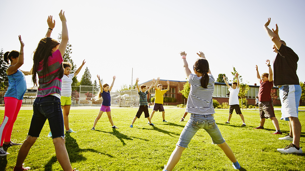 Kids doing exercises on a grassy field outside