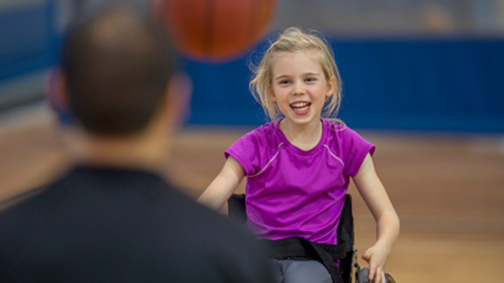 girl in wheelchair playing catch