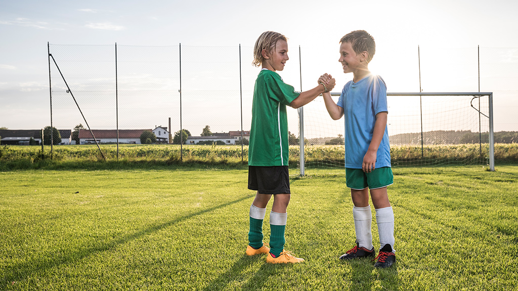 two children greeting each other on soccer field