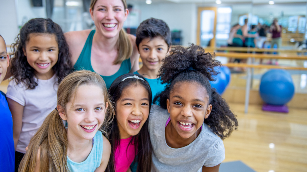 Happy children with yoga instructor in studio - Sanford fit