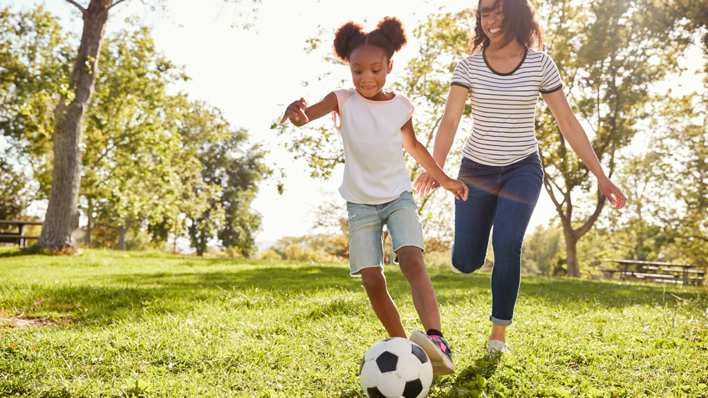 Parent playing soccer with a child - Sanford fit