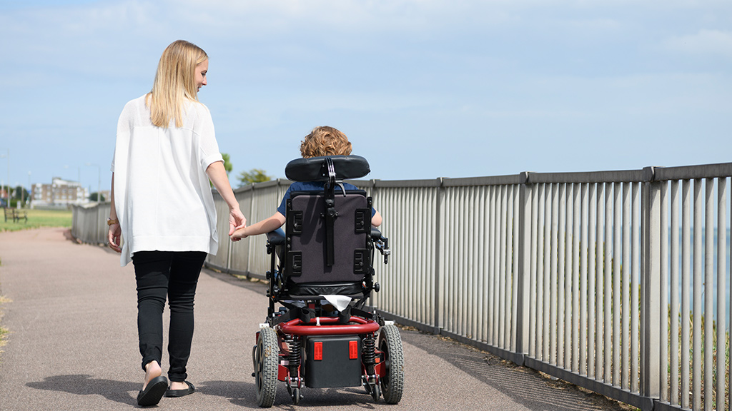 adult walking with child in a wheelchair outside