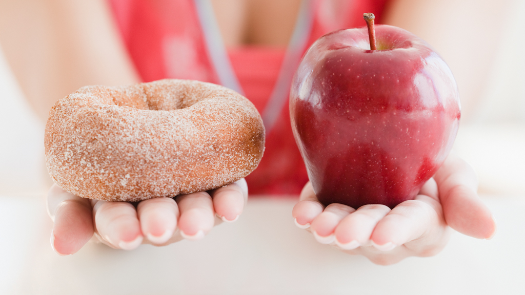 One hand holding a doughnut and the other hand holding an apple - Sanford fit