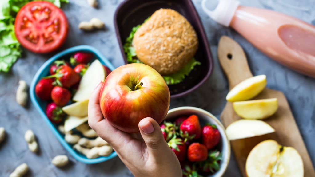 Packing different food containers with healthy foods - Sanford fit