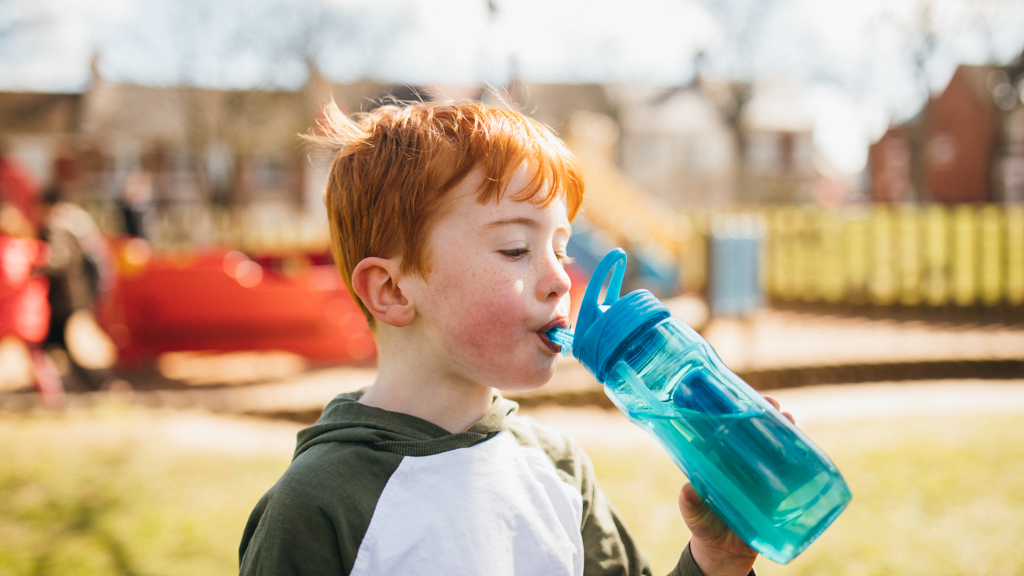 Child outside drinking out of a water bottle - Sanford fit