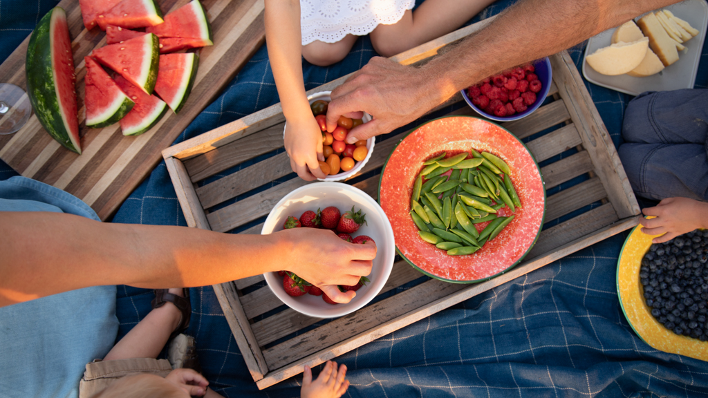 Hands reaching into bowls of fruits and vegetables - Sanford fit