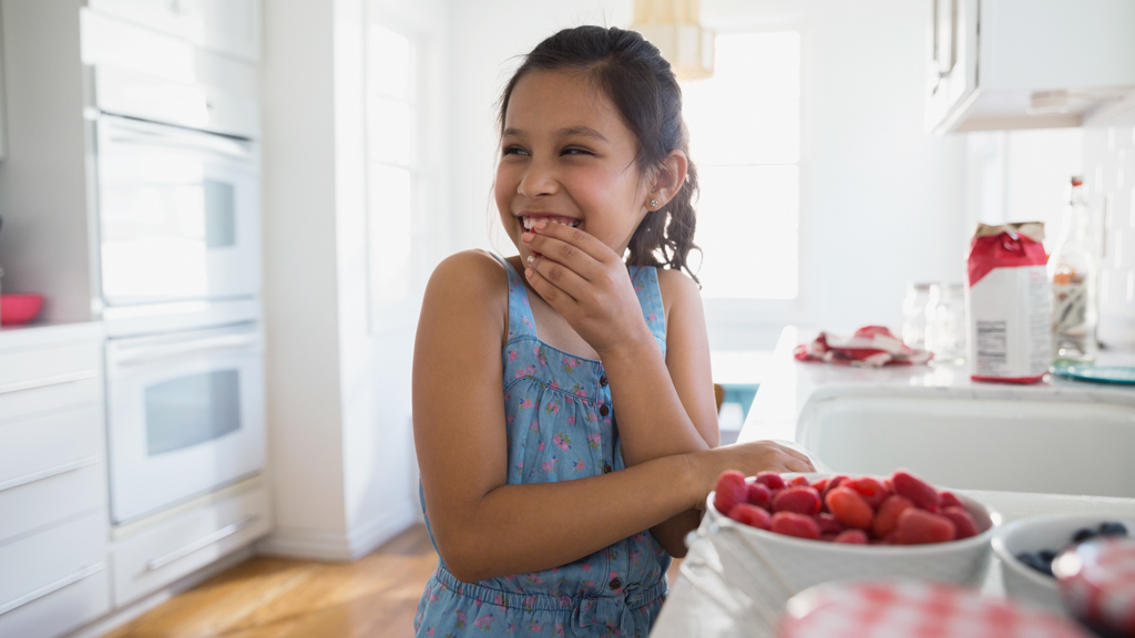 Child in kitchen eating raspberries - Sanford fit