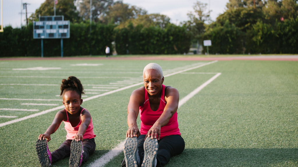 Parent and child stretching on a football field - Sanford fit