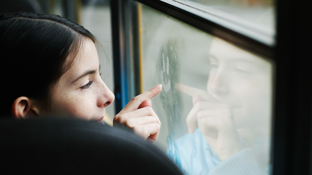 Child drawing a smiley face on a frosted over bus window - Sanford fit