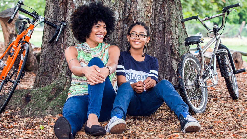 Parent and child sitting under a tree after a bike ride - Sanford fit