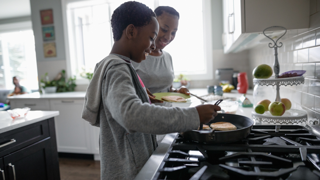 Parent and child cooking over the stove - Sanford fit