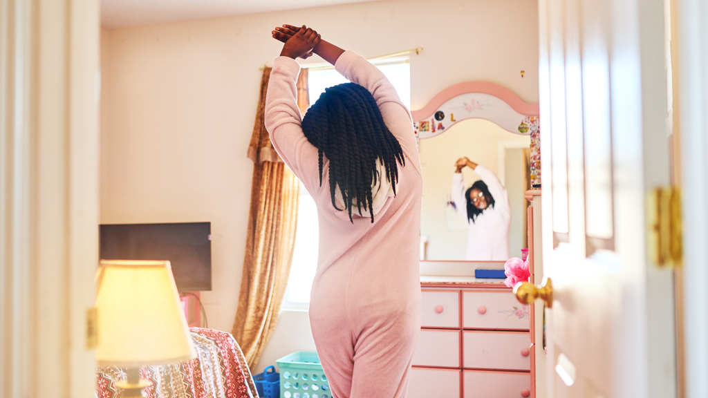 Child stretching in a bedroom mirror-  Sanford fit