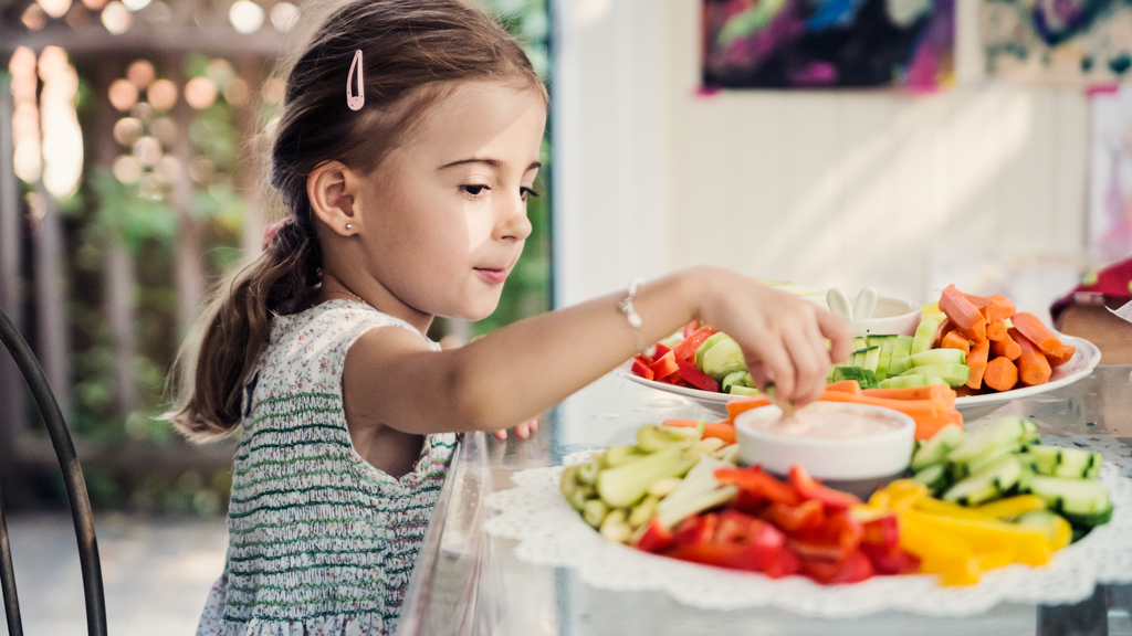 Child picking vegetables from a plate full of vegetables - Sanford fit