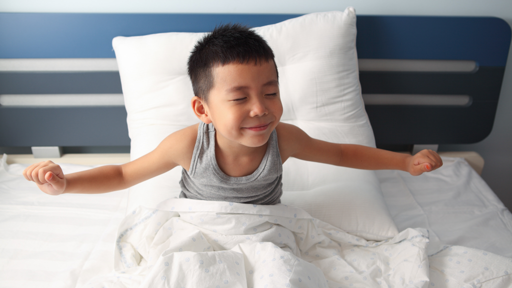 Child sitting up and stretching in bed - Sanford fit