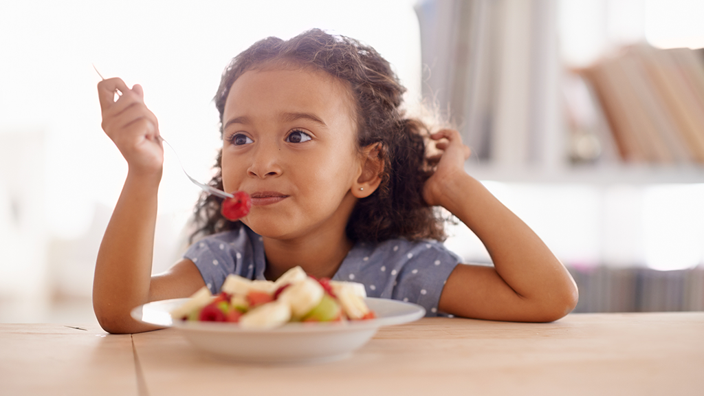 Child eating healthy fruit - Sanford fit
