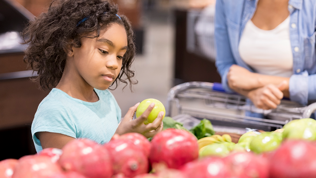 Child examining fruit - Sanford fit