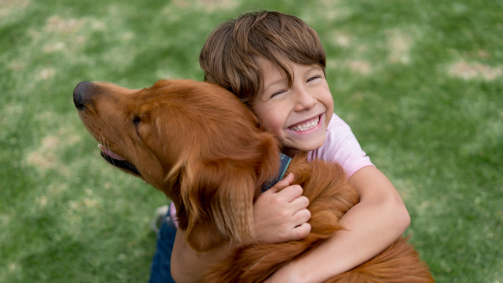 Happy child hugging dog - Sanford fit