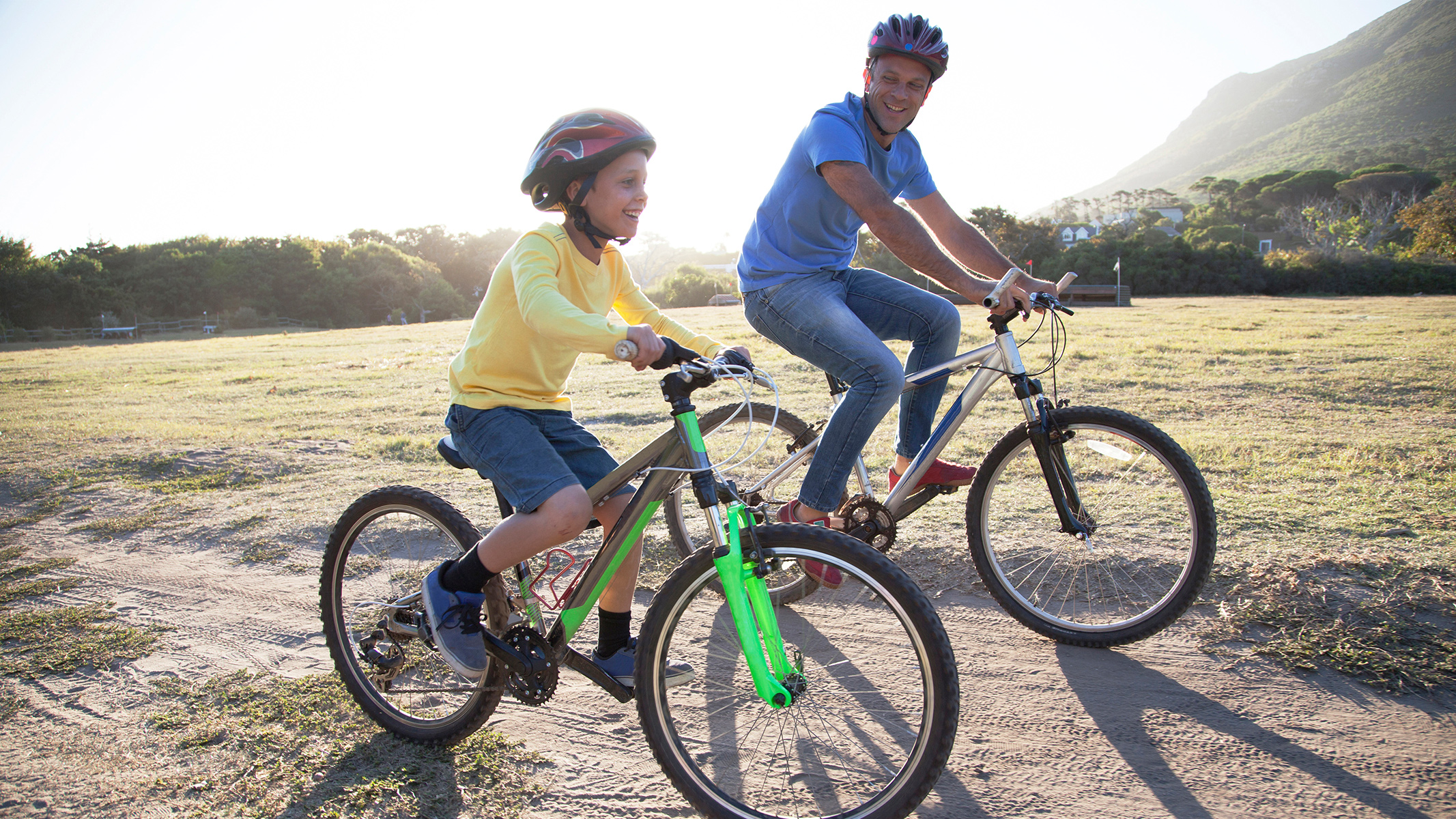 child and guardian riding bikes together outdoors-Sanford Fit