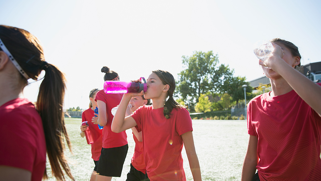 Young athletes drinking water outdoors-Sanford Fit