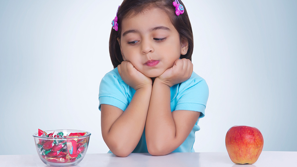 Girl deciding between candy and an apple