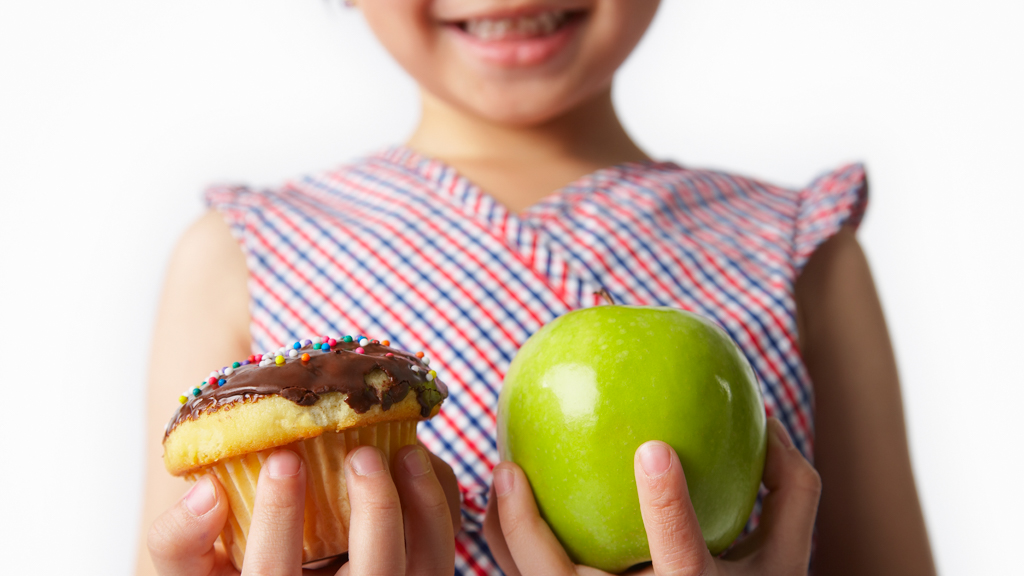 Child choosing between cupcake and apple - Sanford fit