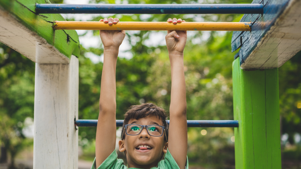 Child playing on monkey bars playground - Sanford fit