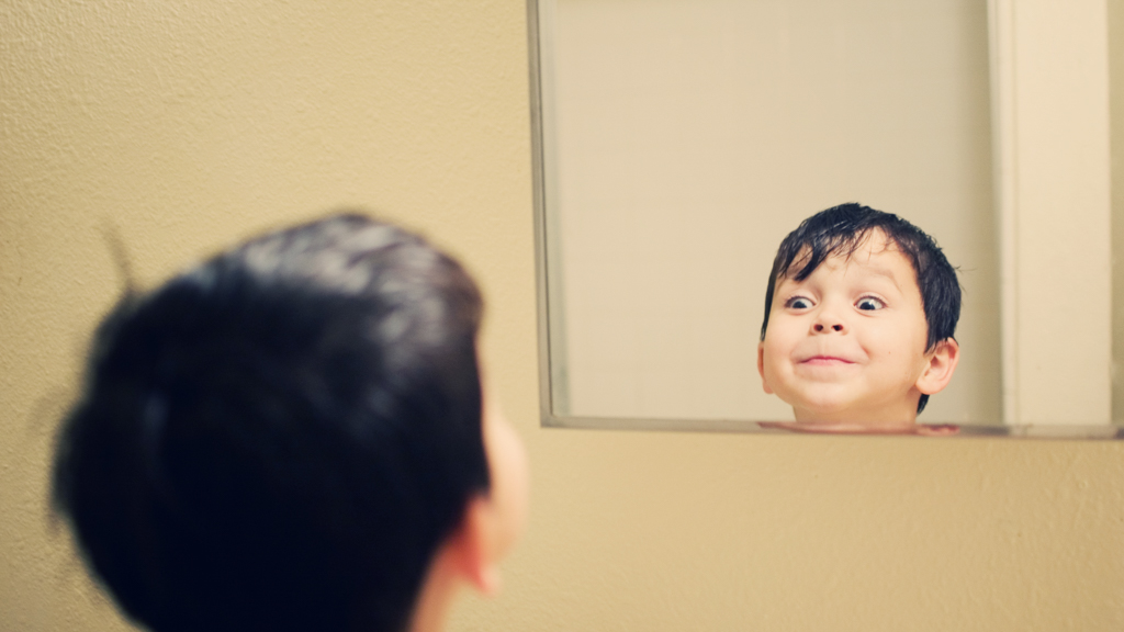 Child making silly face at mirror - Sanford fit